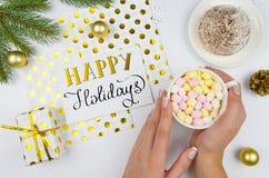 приветствие рождества карточки веселое Женщина держа чашку с зефирами на белой таблице с ветвями ели, подарочной коробке и Стоковые Изображения