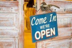 Приведенный внутри мы открыты на деревянной двери открытой Стоковые Фотографии RF