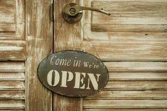 Приведенный внутри мы открыты на деревянной двери, copyspace на праве, v Стоковая Фотография