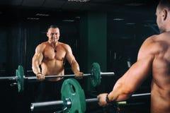 Приведите атлетического культуриста в действие парня разрабатывая бицепс с штангой перед зеркалами, в темном спортзале Стоковое фото RF