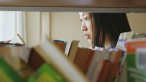 Привлекательная азиатская девушка студента стоя близко полка с книгами в книге удерживания университетской библиотеки кантуя стра акции видеоматериалы