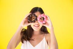 Привлекательная азиатская женщина держа 2 donuts с милым усмехаясь expr стоковое фото rf
