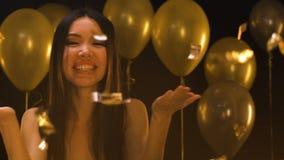 Привлекательная азиатская женщина отправляя поцелуй воздуха в камеру под падая confetti, партией сток-видео
