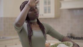 Привлекательная Афро-американская женщина с dreadlocks работая в кухне, она уставшая и обтирает ее лоб с ей сток-видео