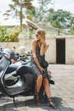 привлекательная белокурая женщина сидя на мотоцикле в городе стоковые изображения