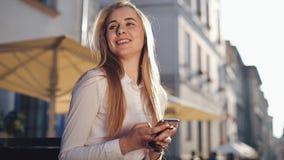 Привлекательная бизнес-леди sitiing на стенде используя сети связи smartphone интернет онлайн социальной соединяясь акции видеоматериалы