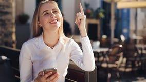 Привлекательная бизнес-леди sitiing на стенде используя сети связи smartphone интернет онлайн социальной соединяясь видеоматериал