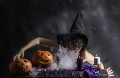 Привлекательная ведьма в wizarding логове при дым идя от ее рта Стоковые Изображения RF