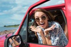 привлекательная возбужденная девушка в солнечных очках показывая жестами и сидя в автомобиле стоковые фото