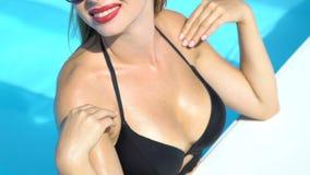 Привлекательная дама в черном бикини штрихуя грудь, загорая в бассейне сток-видео