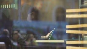 Привлекательная дама в hijab работая на планшете, сидя в кафе, независимый проект акции видеоматериалы