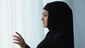Привлекательная дама в hijab смотря окно, исламское повиновение, ждать супруга акции видеоматериалы