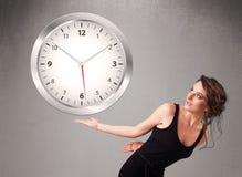Привлекательная дама держа огромные часы Стоковое Фото