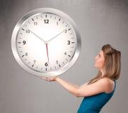 Привлекательная дама держа огромные часы Стоковая Фотография