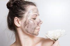 Привлекательная девушка брюнет с белым цветком в лицевой маске Чистка и защита кожи стороны прикладывать политуру кожи внимательн Стоковые Фото