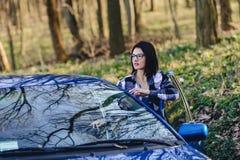 привлекательная девушка водителя смотрит из открыть двери автомобиля Стоковые Фотографии RF