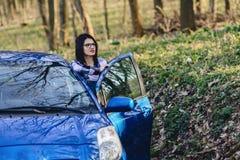 привлекательная девушка водителя смотрит из открыть двери автомобиля Стоковая Фотография