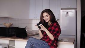 Привлекательная девушка в ее 20 ` s усмехается пока смотрящ через фото на ее камере видеоматериал