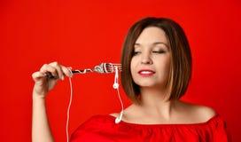 Привлекательная девушка в красном платье держа вилку в руках на штепсельной вилке наушников подготовил съесть стоковые фото
