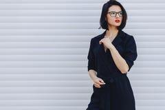 привлекательная девушка в черной кожаной куртке на светлой предпосылке стоковое фото
