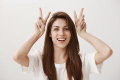 Привлекательная девушка делая цитаты воздуха Портрет очаровательного молодого женского повышения вручает около головы и показа v  стоковое изображение rf