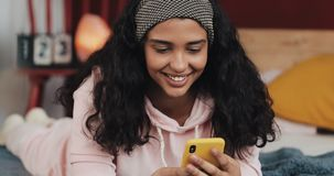 Привлекательная девушка держа кредитную карточку и используя смартфон на кровати Счастливый ходить по магазинам молодой женщины о акции видеоматериалы