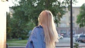 Привлекательная девушка идя вниз по улице в город, повороты к камере и улыбки Красивая блондинка в лучах  сток-видео