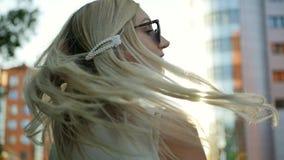 Привлекательная девушка идя вниз по улице в город, повороты к камере и улыбки Красивая блондинка в лучах  видеоматериал