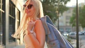 Привлекательная девушка идя вниз по улице в город, повороты к камере и улыбки Красивая блондинка в лучах  акции видеоматериалы