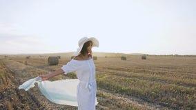 Привлекательная девушка себя smili в длинном платье, большая шляпа с шарфом закручивает вокруг в поле на лето захода солнца бобра сток-видео
