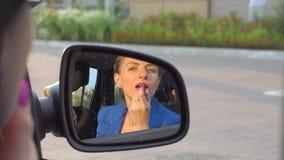 Привлекательная девушка сидит в автомобиле и использует губную помаду Она делает состав для ее губ девушка смотрит зеркало видеоматериал