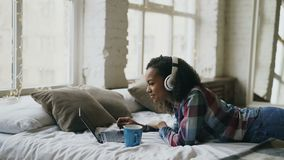 Привлекательная девушка смешанной гонки слушает к музыке пока занимающся серфингом социальные средства массовой информации на ком видеоматериал