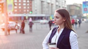 Привлекательная девушка с кофе в вечере, стоя в центре города около дороги акции видеоматериалы