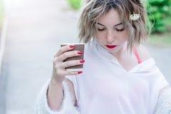 Привлекательная девушка с красными губами и маникюром сидит в парке и выпивая кофе стоковые изображения