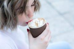 Привлекательная девушка с красными губами принимает глоточек кофе от бумажного стаканчика стоковое фото