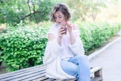 Привлекательная девушка с красными губами сидит в парке с бумажным стаканчиком кофе стоковые изображения rf