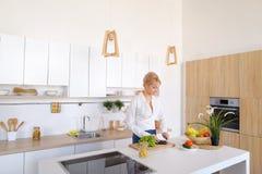 Привлекательная женская домохозяйка режет огурец с ножом и улыбками, Стоковые Изображения RF