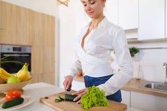 Привлекательная женская домохозяйка режет огурец с ножом и улыбками, Стоковое Изображение RF
