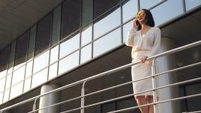 Привлекательная женщина брюнет идя около делового центра и говоря на телефоне Стильный взгляд, элегантная белая блузка сток-видео