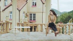 Привлекательная женщина в бежевом катании пальто на качании во дворе  европейского замка видеоматериал