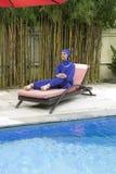 Привлекательная женщина в мусульманском burkini swimwear на кровати планки пляжа около бассейна Стоковая Фотография RF