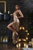 Привлекательная женщина в платье золота около студии рождественской елки стоковая фотография