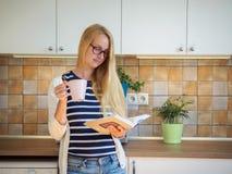 Привлекательная женщина в стеклах держа чашку кофе и читая книгу Стоковая Фотография RF