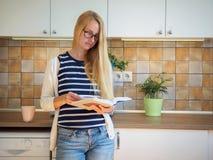 Привлекательная женщина в стеклах читая книгу на кухне Стоковые Фото