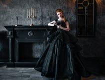 Привлекательная женщина в черном платье в средневековом интерьере стоковые фото