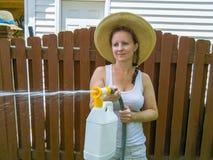 Привлекательная женщина в шляпе используя спрейер давления Стоковое Изображение