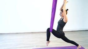 Привлекательная женщина делая антигравитационные тренировки йоги в студии сток-видео