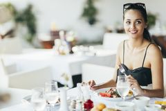 Привлекательная женщина есть в ресторане стоковое изображение