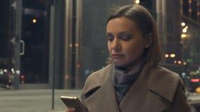 Привлекательная женщина идя вечером со смартфоном в руках, читая электронную почту акции видеоматериалы