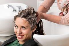 Привлекательная женщина имея ее волосы быть помытым стоковые фотографии rf